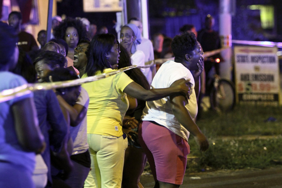 Photo - Family members react as they watch investigators at the scene of a fatal accident on Roosevelt Boulevard in the Olney section of Philadelphia on Tuesday evening July 16, 2013.  Philadelphia police are investigating whether cars may have been drag racing when a mother and two young sons were struck and killed attempting to cross a busy highway. The woman's two other sons ages 4 and 5 are in critical condition. (AP Photo/ Joseph Kaczmarek)