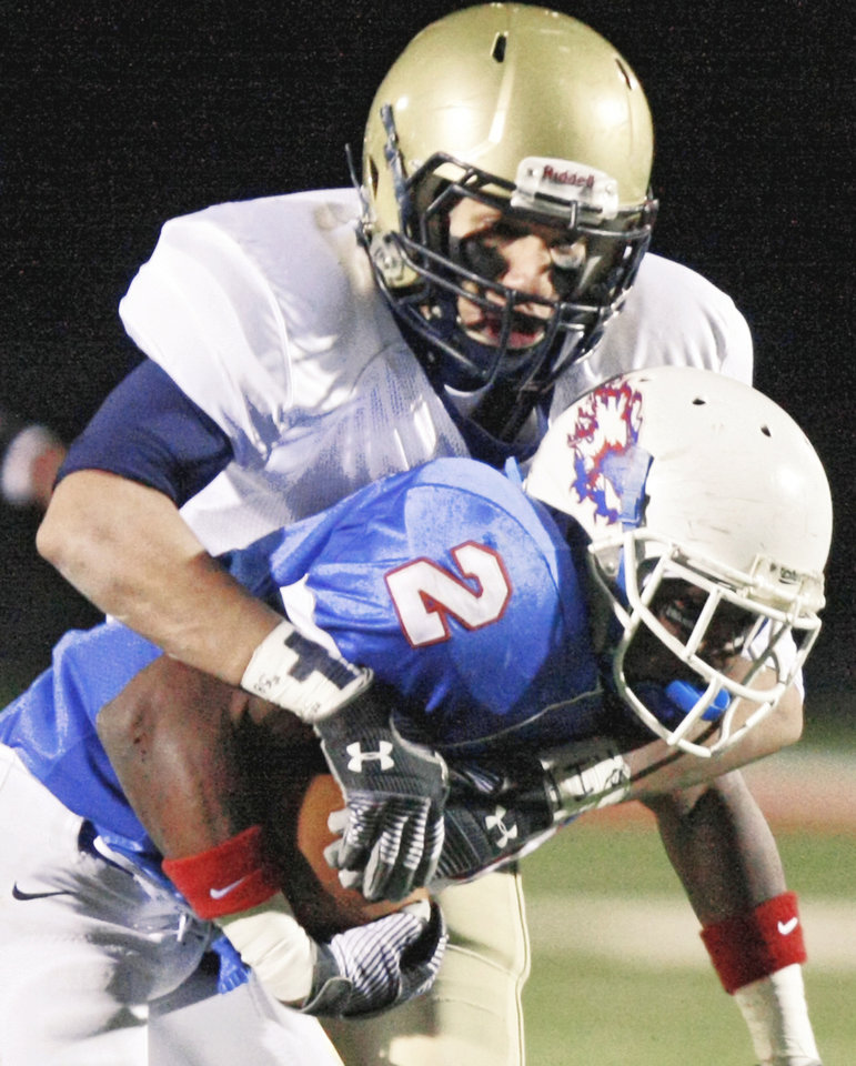 Photo - Kingfisher's Jordan Woods, top, brings down Millwood's Emilio Gatewood during Saturday's game. Photo by Chris Landsberger, The Oklahoman