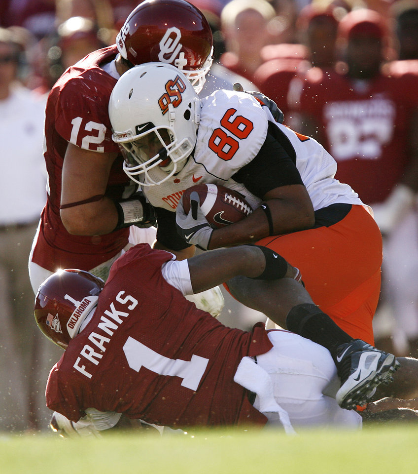Photo - Oklahoma's Austin Box (12) and Dominique Franks (1) bring down OSU's Wilson Youman (86) during the second half of the Bedlam college football game between the University of Oklahoma Sooners (OU) and the Oklahoma State University Cowboys (OSU) at the Gaylord Family-Oklahoma Memorial Stadium on Saturday, Nov. 28, 2009, in Norman, Okla.Photo by Chris Landsberger, The Oklahoman