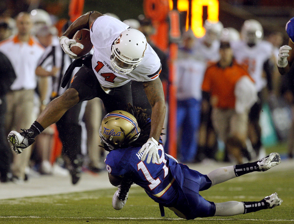 Photo - Oklahoma State's Justin Horton (14) leaps over Tulsa's Milton Howell (19)during a college football game between the Oklahoma State University Cowboys and the University of Tulsa Golden Hurricane at H.A. Chapman Stadium in Tulsa, Okla., Sunday, Sept. 18, 2011. Photo by Sarah Phipps, The Oklahoman