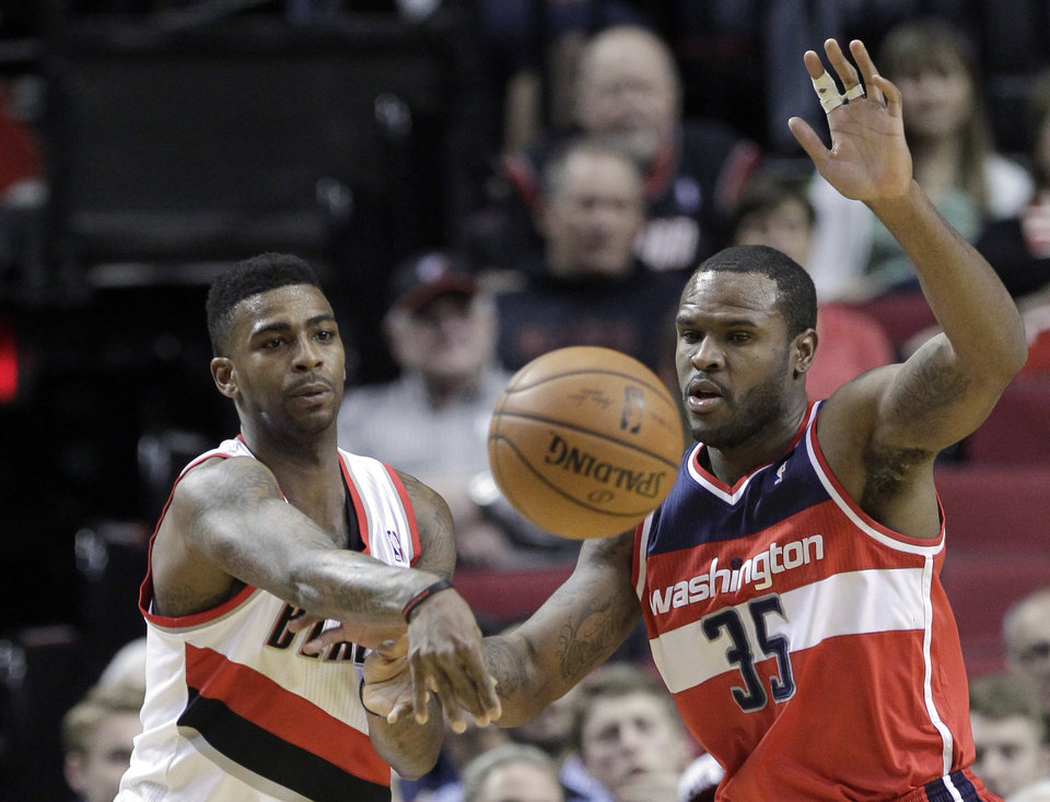 Photo - Portland Trail Blazers forward Dorell Wright, left, passes off against Washington Wizards forward Kevin Seraphin, from French Guiana, during the first half of an NBA basketball game in Portland, Ore., Thursday, March 20, 2014. (AP Photo/Don Ryan)