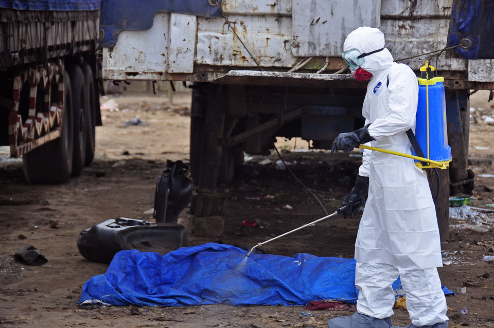 Photo - The body of a man found in the street, suspected of dying from the ebola virus is sprayed with disinfectant, in the capital city of Monrovia, Liberia, Tuesday, Aug. 12, 2014. The World Health Organization declared it's ethical to use untested drugs and vaccines in the ongoing Ebola outbreak in West Africa although the tiny supply of one experimental drug handed out to three people has been depleted and it could be many months until more is available. (AP Photo/Abbas Dulleh)