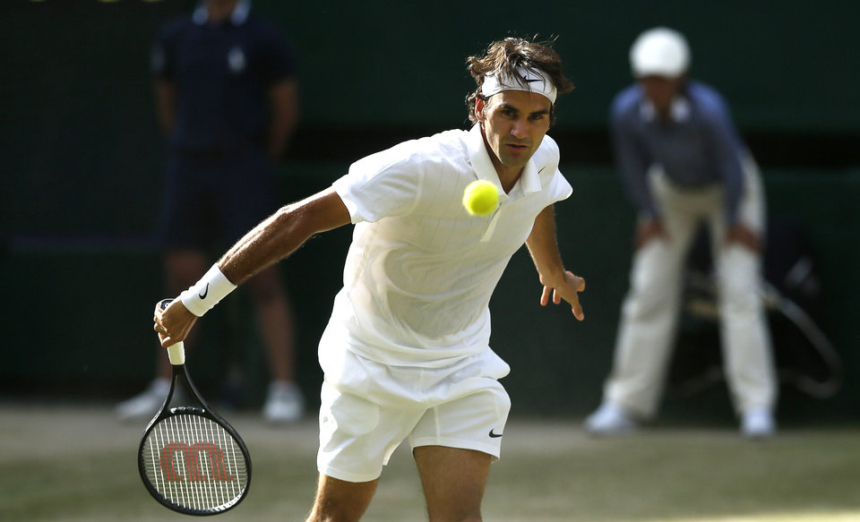 Photo - Roger Federer of Switzerland watches a return over the net to Milos Raonic of Canada during their men's singles semifinal match at the All England Lawn Tennis Championships in Wimbledon, London, Friday, July 4, 2014. (AP Photo/Ben Curtis)