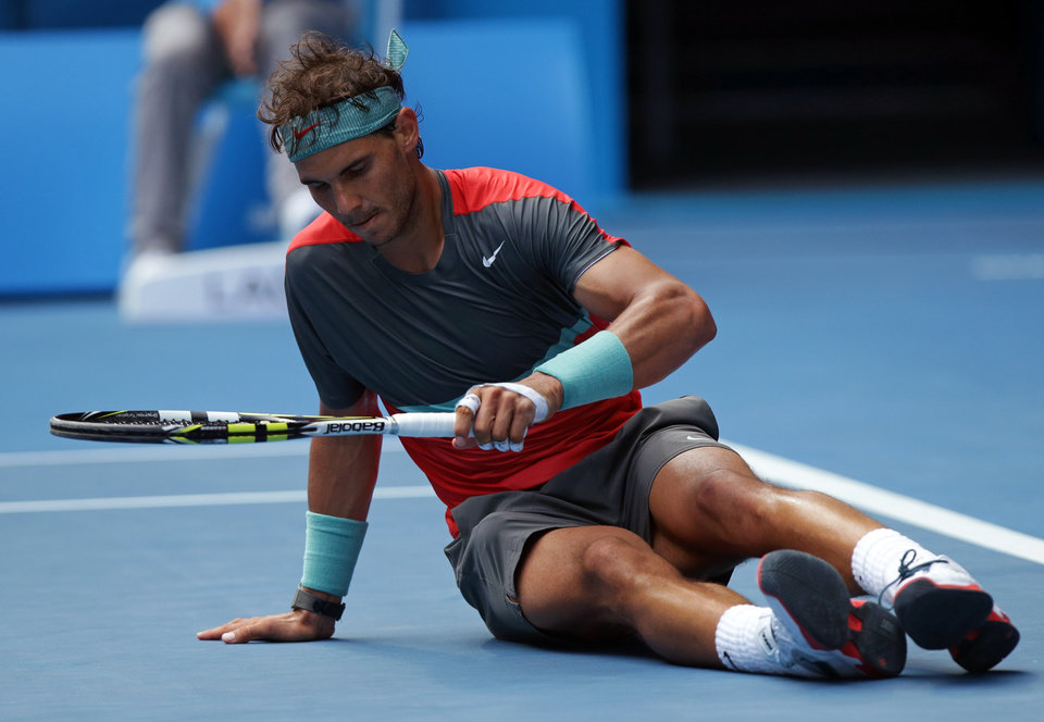 Photo - Rafael Nadal of Spain gets up after he fell   during his fourth round match against Kei Nishikori of Japan at the Australian Open tennis championship in Melbourne, Australia, Monday, Jan. 20, 2014.(AP Photo/Aaron Favila)