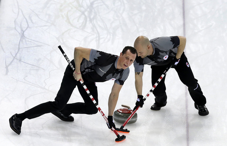 Photo - Canada's E.J. Harnden, left, and Ryan Fry, right, sweep ahead of the rock during the men's curling semifinal game against China at the 2014 Winter Olympics, Wednesday, Feb. 19, 2014, in Sochi, Russia. (AP Photo/Wong Maye-E)