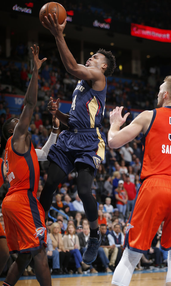 Photo - New Orleans' Buddy Hield (24) drives to the basket as Oklahoma City's Victor Oladipo (5) defends during the NBA game between the Oklahoma City Thunder and the New Orleans Pelicans at the Chesapeake Energy Arena,  Sunday, Dec. 4, 2016. Photo by Sarah Phipps, The Oklahoman