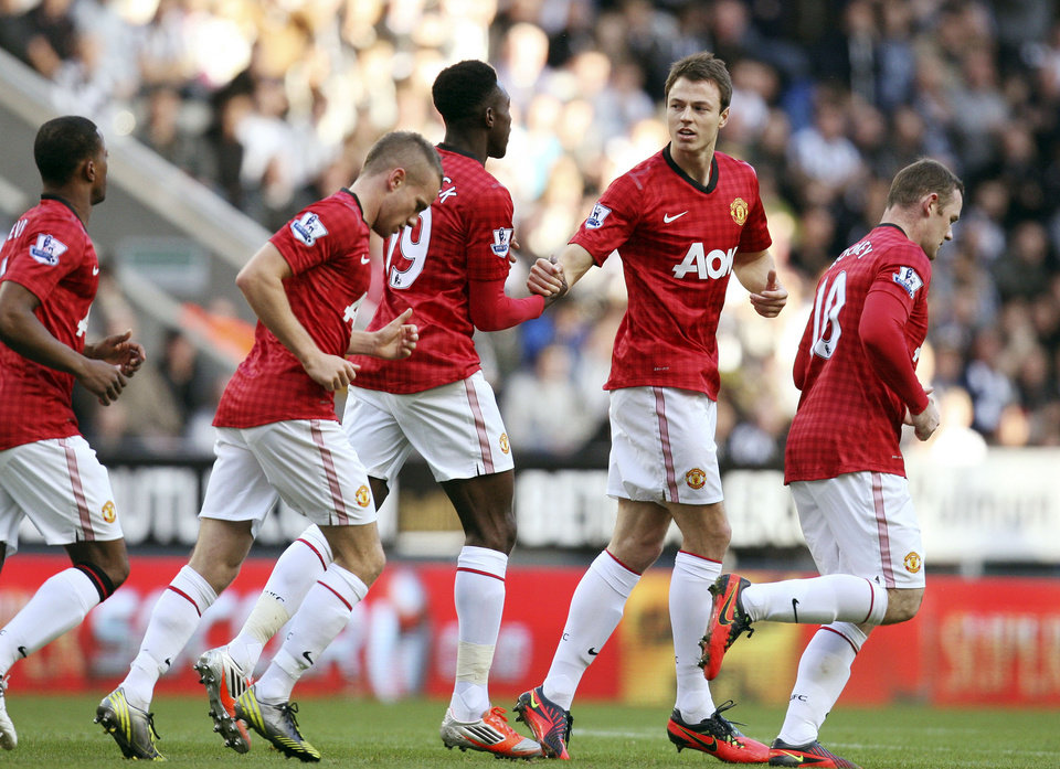 Manchester United's Jonny Evans, second right, celebrates his goal with his teammates during their English Premier League soccer match against Newcastle United at the Sports Direct Arena, Newcastle, England, Sunday, Oct. 7, 2012. (AP Photo/Scott Heppell)