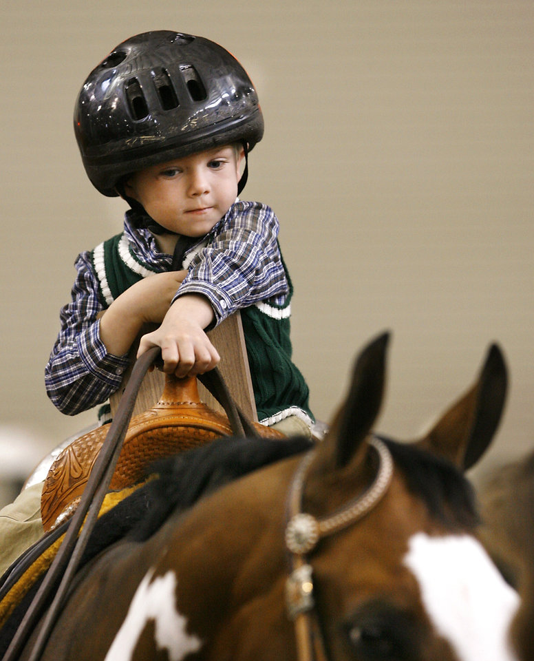 Photo - Jimmy, 4, (his last name cannot be used because he is a foster child) holds the reins of a horse, Patches, in the arena inside Barn 1 at State Fair Park during a special segment called