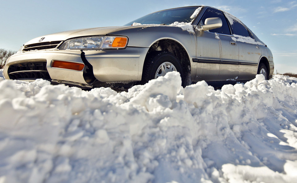 Photo - An abandoned car sits stuck in the snow on Britton Road on Wednesday, Feb. 2, 2011, Oklahoma City, Okla.   Photo by Chris Landsberger, The Oklahoman