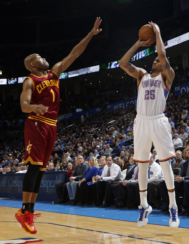 Photo - Oklahoma City's Thabo Sefolosha (25) shoots over Cleveland's Jarrett Jack (1) during the NBA basketball game between the Oklahoma City Thunder and the Cleveland Cavaliers at the Chesapeake Energy Arena in Oklahoma City, Okla. on Wednesday, Feb. 26, 2014.  Photo by Chris Landsberger, The Oklahoman