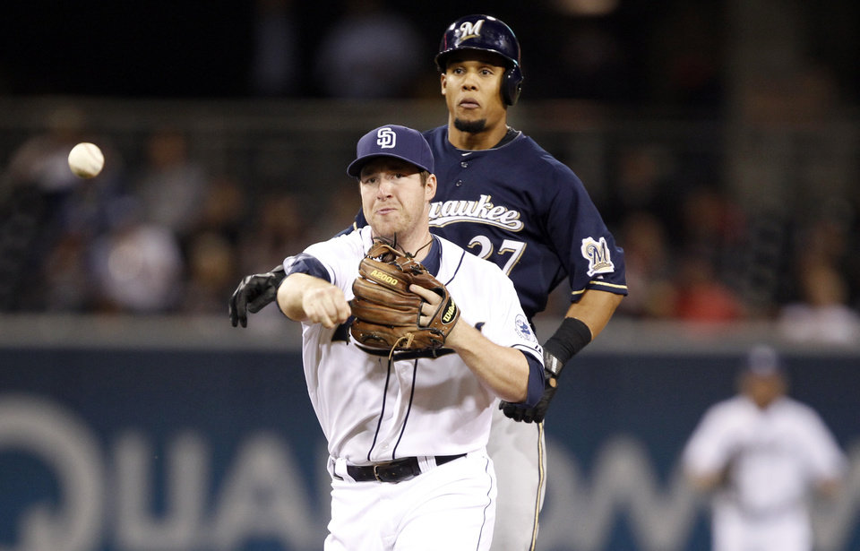 San Diego Padres second baseman Jedd Gyorko, left, makes the relay throw to first to get Milwaukee Brewers' Alex Gonzalez (not pictured), but did not tag Brewers' Carlos Gomez, right, out in time at second base in the fourth inning during a baseball game Monday, April 22, 2013, in San Diego. (AP Photo/Alex Gallardo)