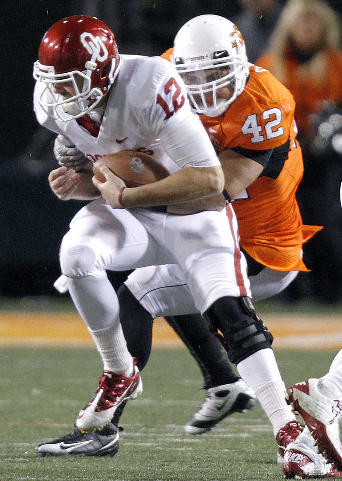 Photo - Oklahoma State's Justin Gent (42) sacks Oklahoma's Landry Jones (12) during the Bedlam college football game between the University of Oklahoma Sooners (OU) and the Oklahoma State University Cowboys (OSU) at Boone Pickens Stadium in Stillwater, Okla., Saturday, Nov. 27, 2010. Photo by Chris Landsberger, The Oklahoman