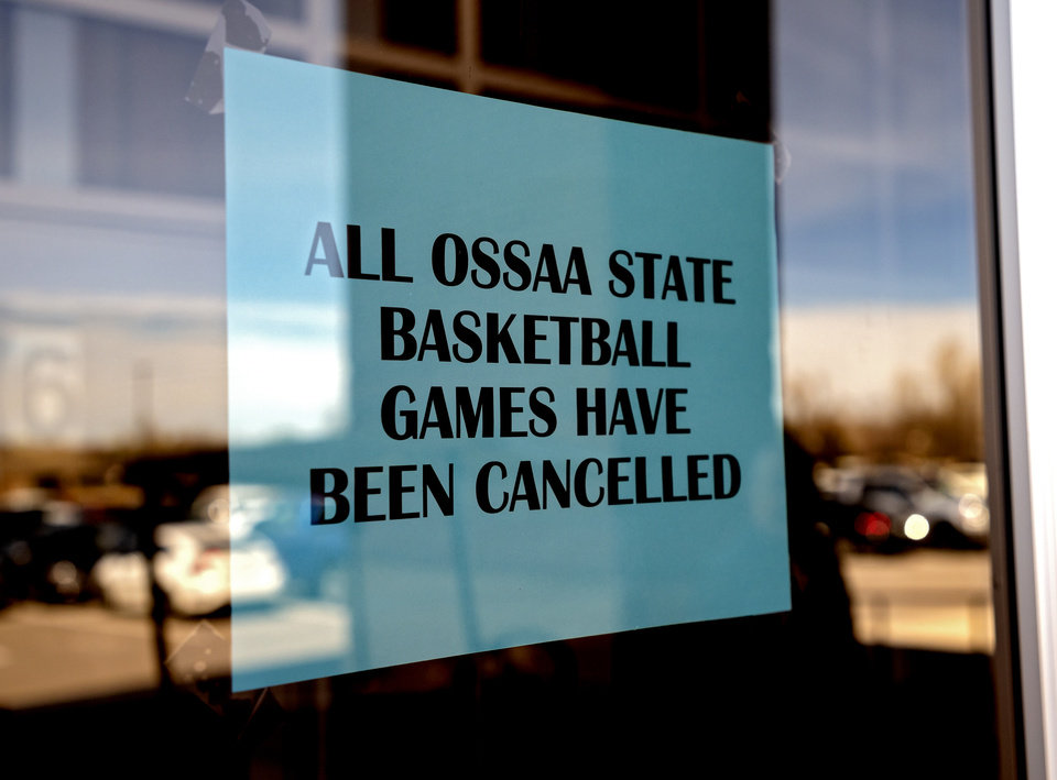 Photo - Signs hang on the door at Yukon High School announcing the cancelation of the Oklahoma Secondary School Activities Association state basketball playoff games at the school in Yukon, Okla. on Thursday, March 12, 2020.   [Chris Landsberger/The Oklahoman]