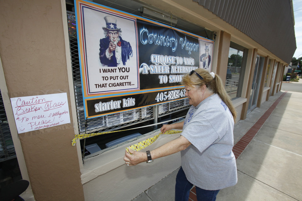 Photo -  Carolyn Deal owner of Country Vapor strings some duct tape across a broken window at her business that was broken in an early morning earthquake in Harrah on Tuesday. Photo by David McDaniel, The Oklahoman   David McDaniel