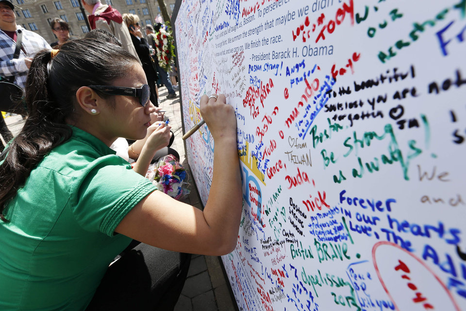 Photo - Michelle Littke, of Scituate, Mass., wites on a poster at a makeshift memorial in Copley Square on Boylston Street in Boston, Wednesday, April 24, 2013. Traffic was allowed to flow all the way down Boylston Street on Wednesday morning for the first time since two explosions on April 15.(AP Photo/Michael Dwyer)