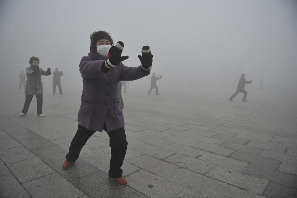 Retirees play Taichi during their morning exercise on a hazy day in Fuyang city, in central China's Anhui province, Monday Jan. 14, 2013. Air pollution is a major problem in China due to the country's rapid pace of industrialization, reliance on coal power, explosive growth in car ownership and disregard for environmental laws. (AP Photo)  CHINA OUT