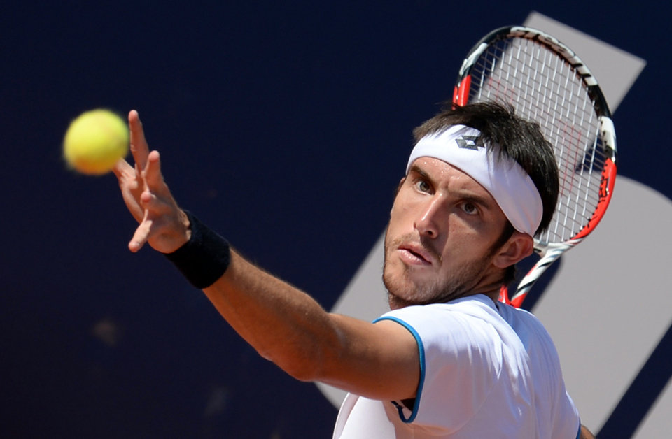 Photo - Leonardo Mayer of Argentina serves to Germany's Philipp Kohlschreiber in their semi final match at the German Open tennis tournament in Hamburg, Germany, Saturday, July 19, 2014. Mayer won the match with 7-5 and 6-4. (AP Photo/dpa, Daniel Reinhardt)