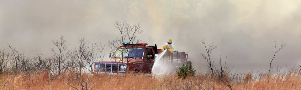Photo - A firefighter on a brush pumper in a field near NE 73 Street and Post Road on a grass fire in Oklahoma City Wednesday, April 6, 2011. Photo by Paul B. Southerland, The Oklahoman