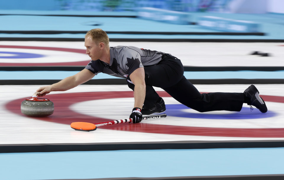 Photo - Canada's skip Brad Jacobs delivers the rock  during the men's curling gold medal game against Britain at the 2014 Winter Olympics, Friday, Feb. 21, 2014, in Sochi, Russia. (AP Photo/Robert F. Bukaty)