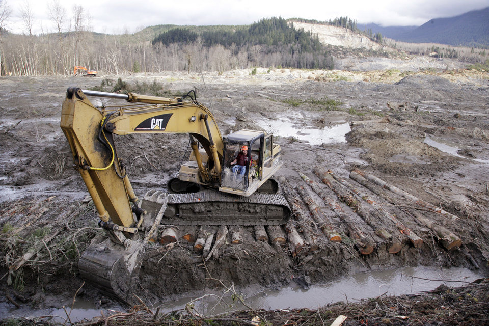 Photo - An excavator clears a drainage channel at the scene of a deadly mudslide, torn loose from the hillside at upper right, Wednesday, April 2, 2014, in Oso, Wash. The March 22 mudslide has killed at least 29 and another 13 are unaccounted for. (AP Photo/Elaine Thompson)
