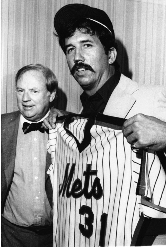 Photo - FILE - In this Oct. 13, 1983 file photo, newly named New York Mets manager Dave Johnson, right, poses with his new uniform jersey and with Mets general manager Frank Cashen after Johnson was introduced at a news conference in Philadelphia. The Mets say Cashen has died. He was 88. The team says Cashen died Monday, June 30, 2014,  at a hospital in Easton, Maryland. (AP Photo, File)