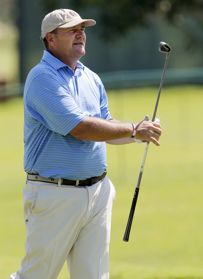 Photo - Rocky Walcher watches his shot from the fairway on the No. 18 during practice rounds for the U.S. Senior Open golf tournament at Oak Tree National in Edmond, Okla., Monday, July 7, 2014. Photo by Nate Billings, The Oklahoman