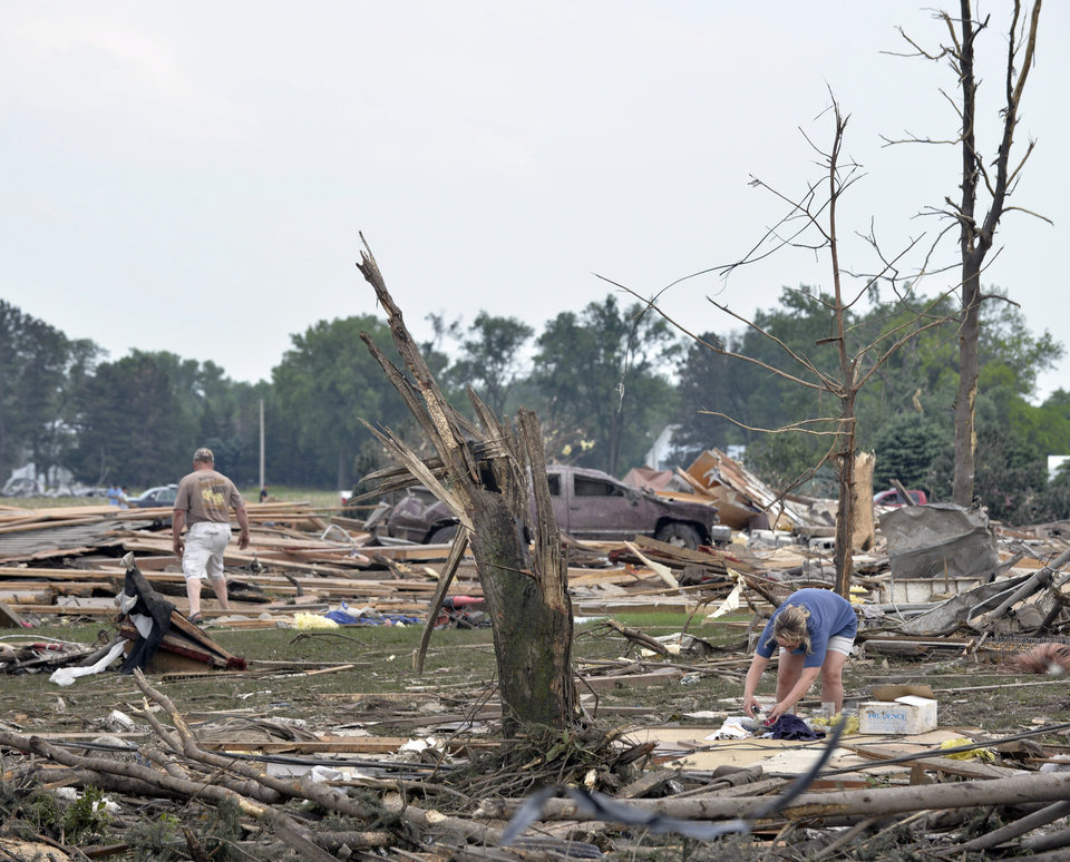 Photo - Jaime, right, and Jeff Hoadley, of Madison, Neb., look over the property next to her parents' home and St. John's Lutheran Church, where Jaime's father is pastor, in Pilger, Neb., after tornadoes moved through the area Monday, June 16, 2014. A storm packing rare dual tornadoes tore through the tiny farming town in northeast Nebraska, killing a 5-year-old girl, leaving grain bins crumpled like discarded soda cans and flattening dozens of homes. (AP Photo/The Norfolk Daily News, Darin Epperly)