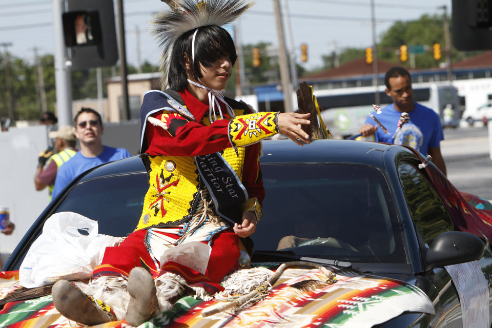 Northern Cheyenne Morning Star Warrior, Marvin Garcia Jr., throws candy to the crowd while he rides through downtown Oklahoma City during the Red Earth parade on Friday, June 7, 2013. Photo by Aliki Dyer, The Oklahoman