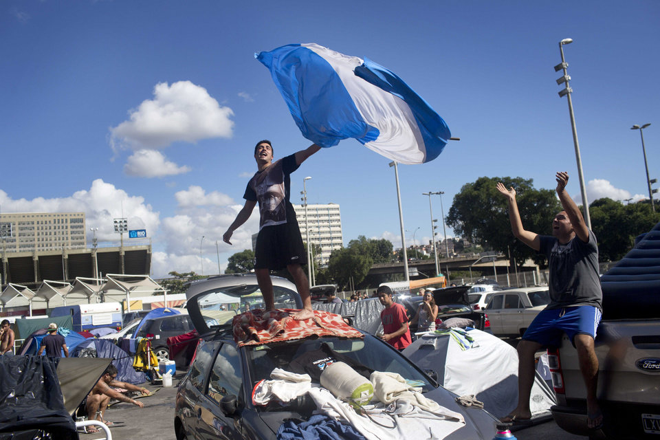 Photo - An Argentina soccer fan waves an Argentine flag from the top of a car in Samba Land, an area visiting World Cup fans are using as a campground, on the final day of the tournament in Rio de Janeiro, Brazil, Sunday, July 13, 2014. Argentina will face Germany on Sunday. (AP Photo/Rodrigo Abd)
