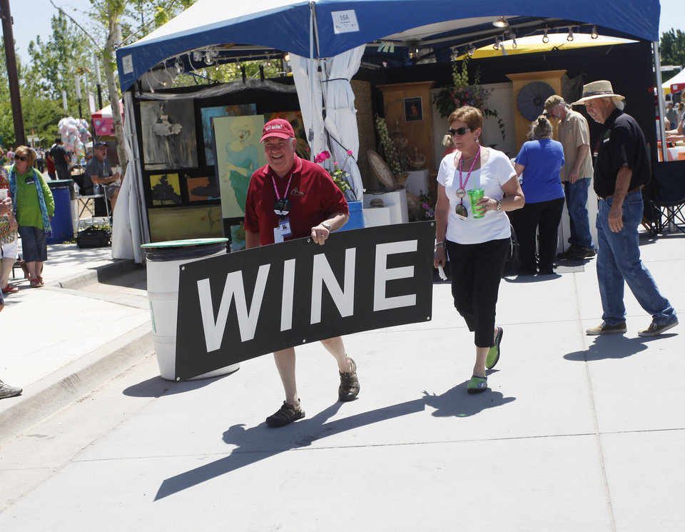 Photo - John Robberson and his wife Lynn Robberson carry a sign to a booth during opening day of the Festival of the Arts in downtown Oklahoma City TUesday, April 24, 2012. The Robbersons are past chairs of the festival. Photo by Doug Hoke, The Oklahoman
