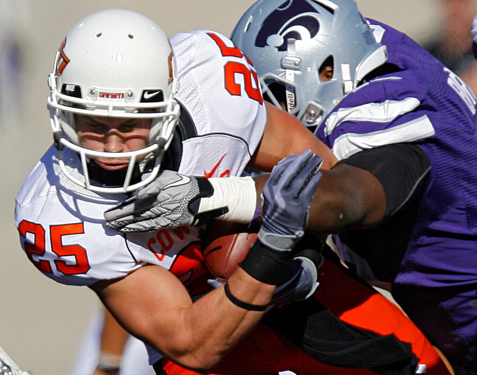 Oklahoma State\'s Josh Cooper (25) is hit by after a reception by a member of the Kansas State defense during the first half of the college football game between the Oklahoma State University Cowboys (OSU) and the Kansas State University Wildcats (KSU) on Saturday, Oct. 30, 2010, in Manhattan, Kan. Photo by Chris Landsberger, The Oklahoman