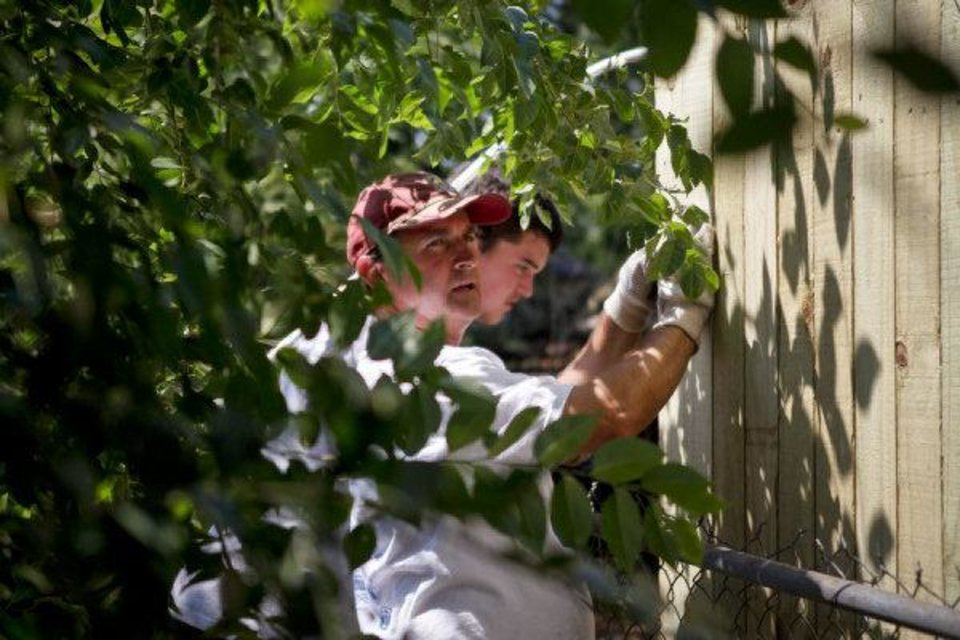 Tim Moran, left, and Grant Matthis, from the Catholic HEART Workcamp adjust a fence panel in the backyard of Dale Osborne in the Riverpark neighborhood in southwest Oklahoma City. ZACH GRAY - THE OKLAHOMAN