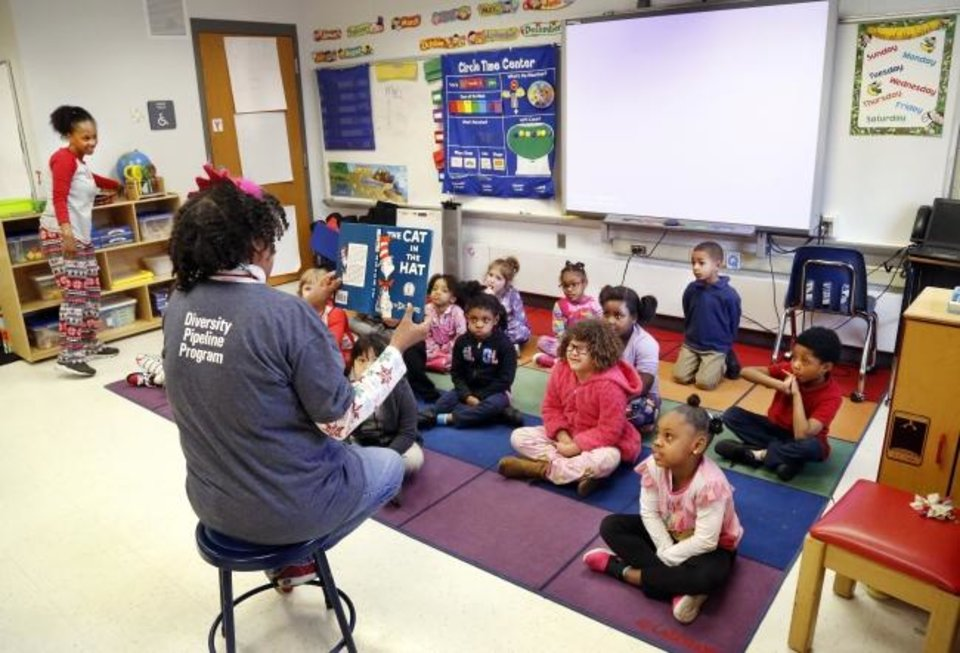 Photo -  Teaching assistant Glorene Stewart reads to kindergarten students at North Highland Elementary on March 8, 2019. Oklahoma City Public Schools is planning to bring pre-K and kindergarten classes back in person this month after starting the school year with online learning. [The Oklahoman Archives]
