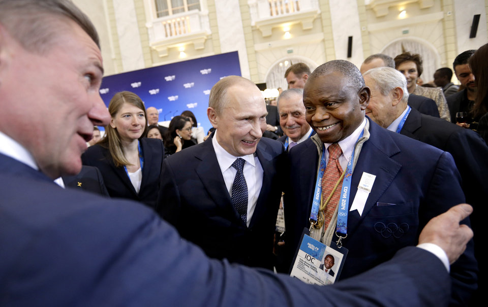 Photo - Russian President Vladimir Putin, center, greets International Olympic Committee members Habu Ahmed Gumel, right, and  executive board member Sergei Bubka, left, at a welcoming event ahead of the upcoming 2014 Winter Olympics at the Rus Hotel, Tuesday, Feb. 4, 2014, in Sochi, Russia. (AP Photo/David Goldman, Pool)