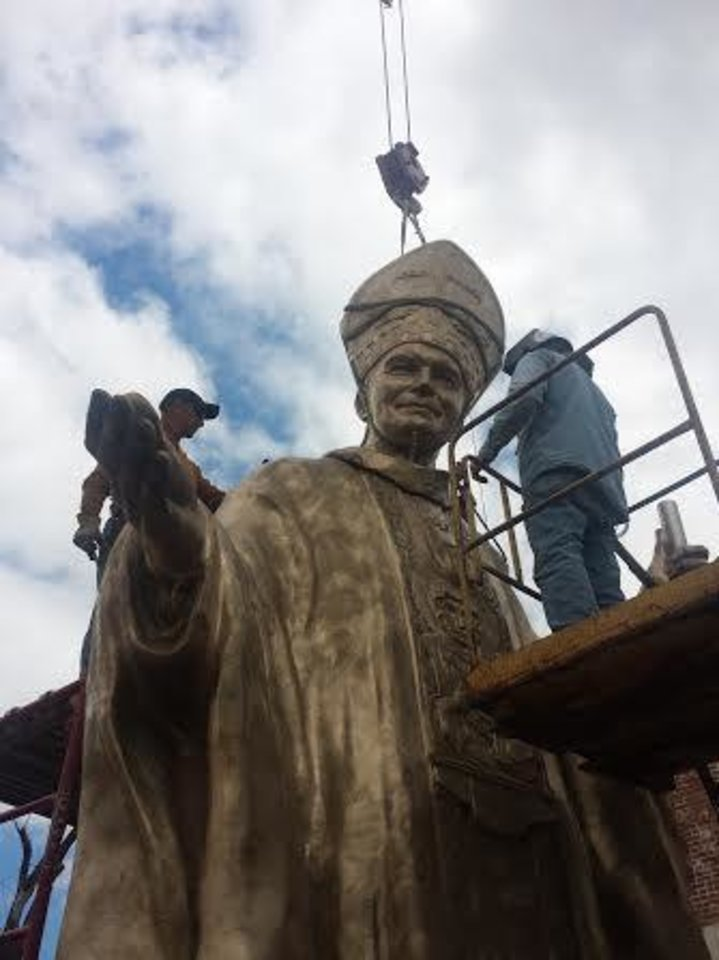 Photo -  Crane operators successfully mount the head of Pope John Paul II onto his bronzed body outside The Crucible foundry in Norman. [PHOTO PROVIDED]