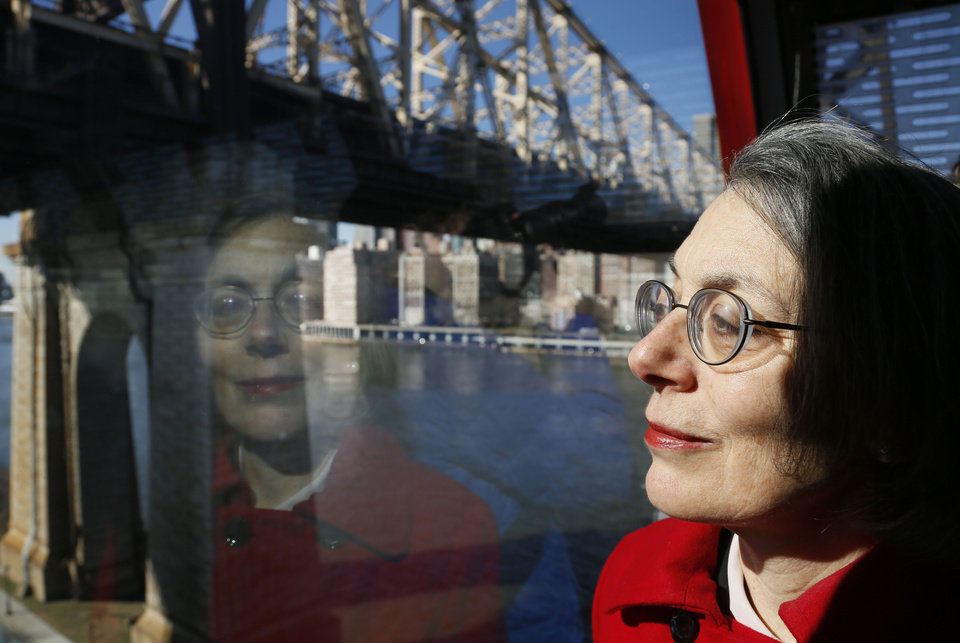 Janet Falk, public relations professional, rides the Roosevelt Island tramway with a Manhattan view behind her on Thursday, Feb. 21, 2013 in New York.  Falk applied for a public-relations job at a New York City law firm two years ago, but the recruiter told her she wouldn�t be considered because she had been unemployed for more than three months, Falk said. (AP Photo/Bebeto Matthews)