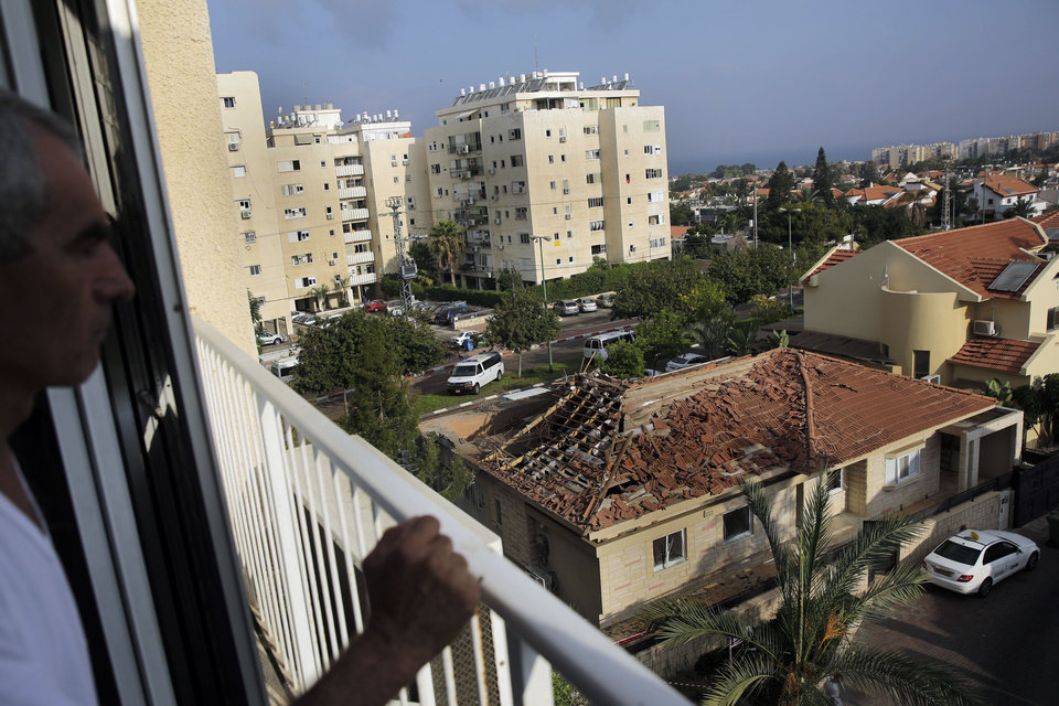 Photo - A man looks at a home hit by a rocket fired from the northern Gaza Strip Tuesday morning in the costal city of Ashkelon, Israel, Tuesday, Aug. 26, 2014. (AP Photo/Tsafrir Abayov)