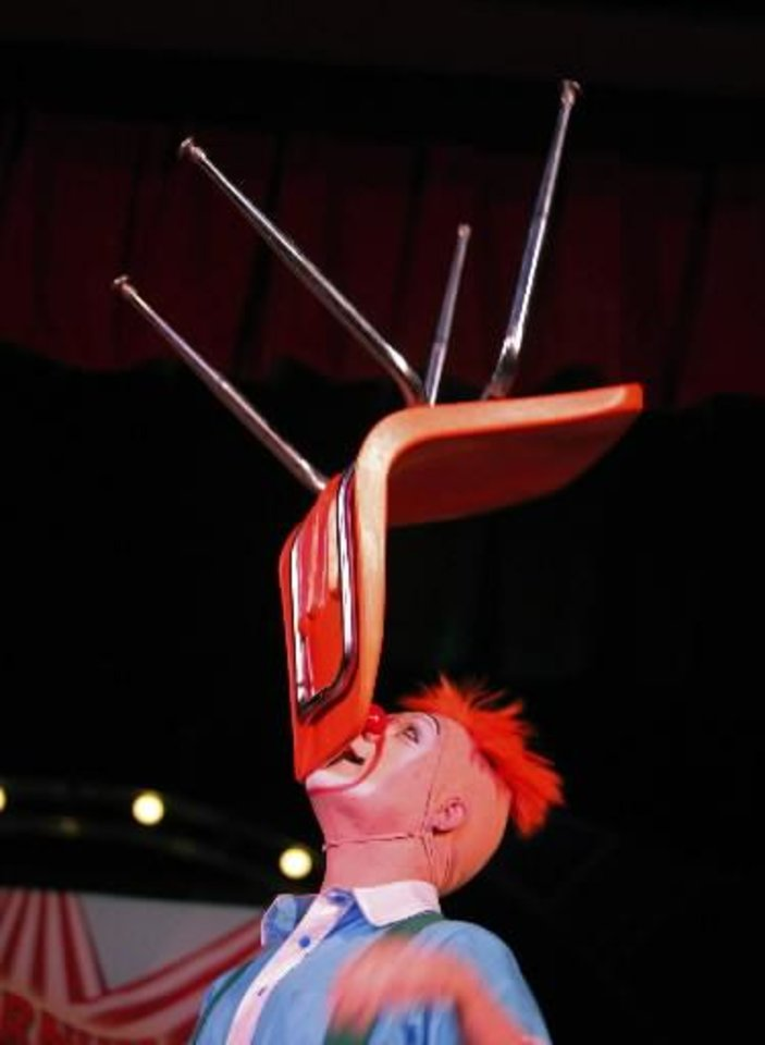 Photo -  Jordan Bunce balances a chair on his chin during a Science Live show att the Science Museum of Oklahoma, Wednesday, June 27, 2012. Ringling Bros. clowns showed viewers the science behind circus performance. Photo by Garett Fisbeck, The Oklahoman