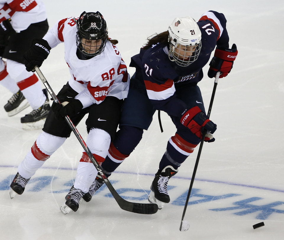 Photo - Hilary Knight of the Untied States takes the puck away from Phoebe Stanz of Switzerland during the second period of the 2014 Winter Olympics women's ice hockey game at Shayba Arena, Monday, Feb. 10, 2014, in Sochi, Russia. (AP Photo/Petr David Josek)