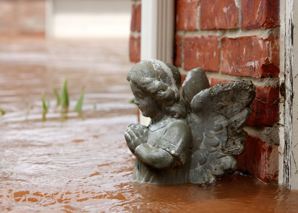 Photo - An angel statue is up to her waist in floodwaters next to this house in the Palo Verde Addition in Edmond, OK. Flood waters inundated a number of homes in the area after record rainfall, Monday, June 14, 2010. By Paul Hellstern, The Oklahoman