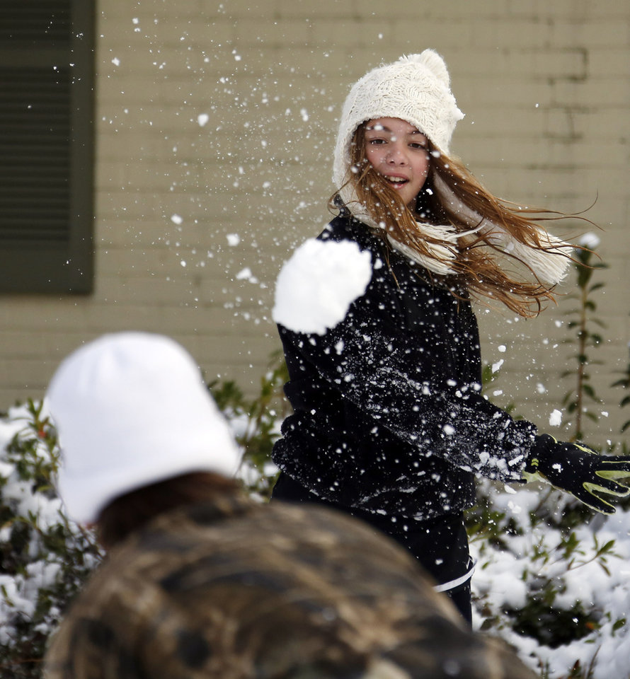 Photo - Skylar Alexander, 11, tosses a snowball at her brother Parker Alexander, 14, outside their Jackson, Miss., home, Thursday,  Jan. 17, 2013.  A winter storm system left 2 to 4 inches of snow in parts of central Mississippi before heading east toward Alabama, the National Weather Service said. (AP Photo/Rogelio V. Solis)