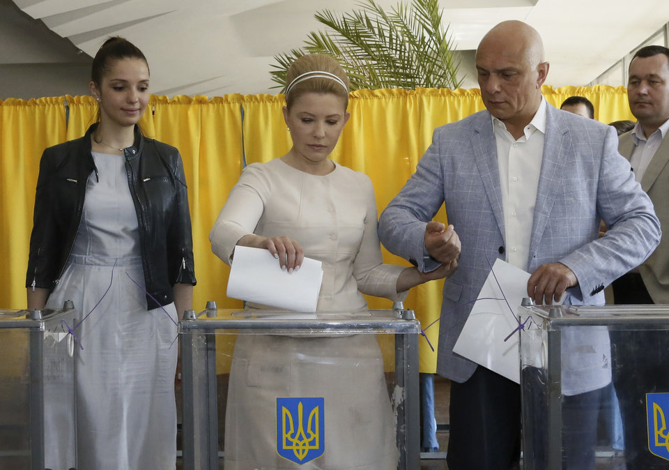 Photo - Ukraine's presidential candidate Yulia Tymoshenko casts her ballot as her husband Oleksandr, right, and daughter Yevgenia assist her at a polling station during presidential election in Dnipropetrovsk, Ukraine, Sunday, May,25, 2014. Ukraine's critical presidential election got underway Sunday under the wary scrutiny of a world eager for stability in a country rocked by a deadly uprising in the east.(AP Photo/Olexander Prokopenko)