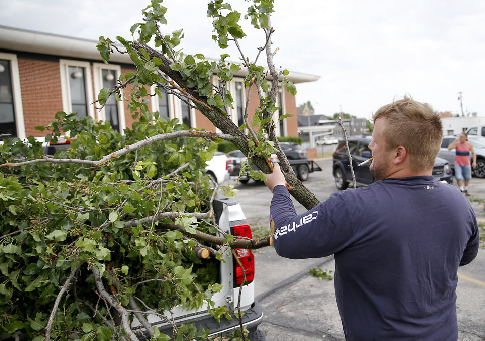 Photo - Heath Wright helps clear tree damage from the Trinity Baptist Church parking lot after an apparent tornado moved through the area in Oklahoma City, Sunday, May 26, 2019. Wright lives in a nearby neighborhood and volunteered to help the church.[Sarah Phipps/The Oklahoman]