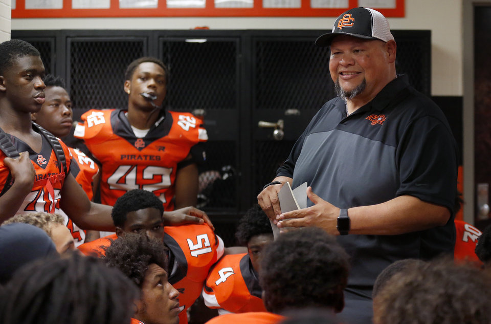 Photo -  The Rev. Mike Keahbone, senior pastor of Cherokee Hills Baptist Church, chats with Putnam City High School football players before a game on Sept. 14 at Putnam City Stadium in Oklahoma City. [Photo by Sarah Phipps, The Oklahoman]