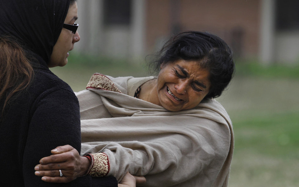 Photo - A Pakistani woman mourns outside a hospital's morgue, where the bodies of victims of a twin suicide bombing are, in Islamabad, Pakistan, Monday, March 3, 2014. Two suicide bombers blew themselves up at a court complex in the Pakistani capital on Monday, killing nearly a dozen and wounding scores in a rare terror attack in the heart of Islamabad, officials said. (AP Photo/Anjum Naveed)