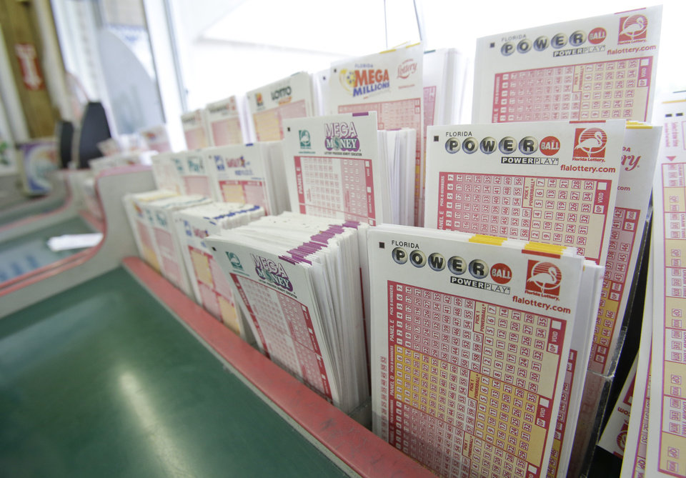 Photo - Powerball tickets, right, along with other lotto tickets are seen Thursday, May 16, 2013, at a convenience store in Orlando, Fla.  The prize estimated around $475 million is the third largest in lottery history, and the winning numbers will be drawn on Saturday.(AP Photo/John Raoux)