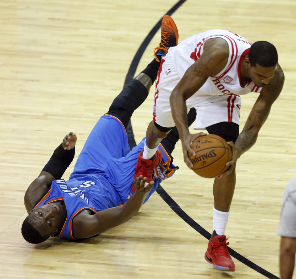 Photo - Oklahoma City's Victor Oladipo (5) and Trevor Ariza (1) scramble for a ball during Game 5 in the first round of the NBA playoffs between the Oklahoma City Thunder and the Houston Rockets in Houston, Texas,  Tuesday, April 25, 2017.  Houston won 105-99. Photo by Sarah Phipps, The Oklahoman