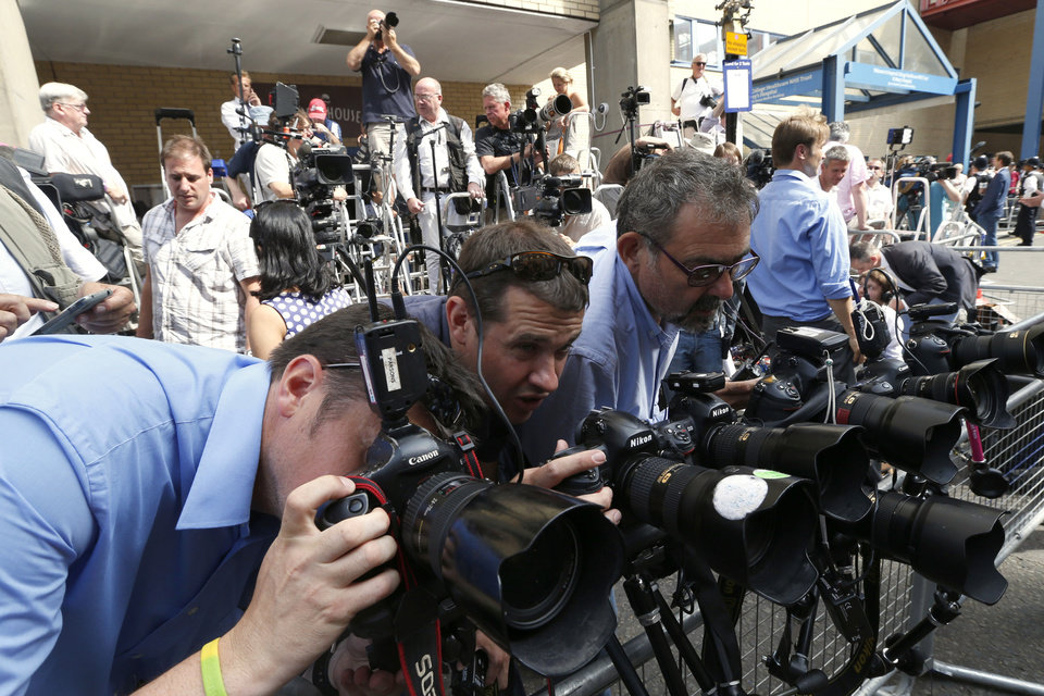 Photo - Photographers adjust their camera's outside St. Mary's Hospital exclusive Lindo Wing in London, Monday, July 22, 2013. Buckingham Palace officials say Prince William's wife, Kate, has been admitted to the hospital in the early stages of labour. Royal officials said that Kate traveled by car to St. Mary's Hospital in central London. Kate, also known as the Duchess of Cambridge, is expected to give birth in the private Lindo Wing of the hospital, where Princess Diana gave birth to William and his younger brother, Prince Harry.The baby will be third in line for the British throne, behind Prince Charles and William, and is anticipated eventually to become king or queen. (AP Photo/Lefteris Pitarakis)