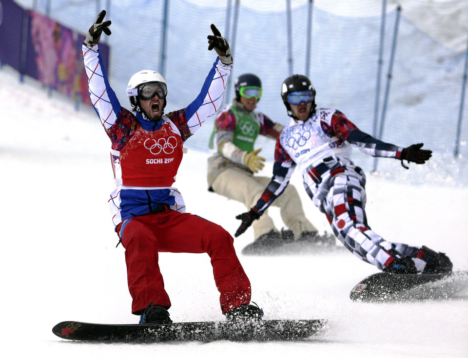 Photo - France's Pierre Vaultier, left, celebrates taking the gold medal ahead of silver medalist Nikolai Olyunin of Russia, right, and bronze medalist Alex Deibold of the United States in the men's snowboard cross final at the Rosa Khutor Extreme Park, at the 2014 Winter Olympics, Tuesday, Feb. 18, 2014, in Krasnaya Polyana, Russia. (AP Photo/Andy Wong, File)