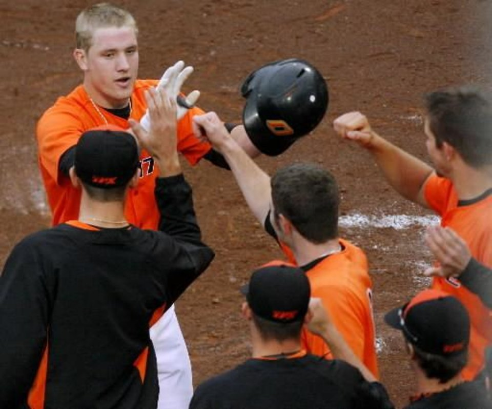Oklahoma State's Kevin David celebrates with his teammates after he scores the go-ahead run against Oklahoma during the fourth inning their game at the AT&T Bricktown Ballpark in Oklahoma City on Sunday, May 10, 2009. The Cowboys beat the Sooners 5-1. Photo by John Clanton